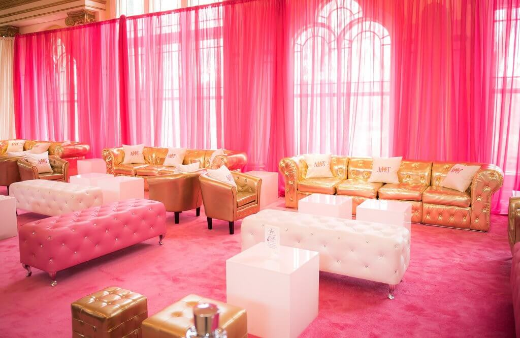 amazingcelebrationsllc.com pink, gold and white lounge area with pink carpets and pink drapery with custom pillows